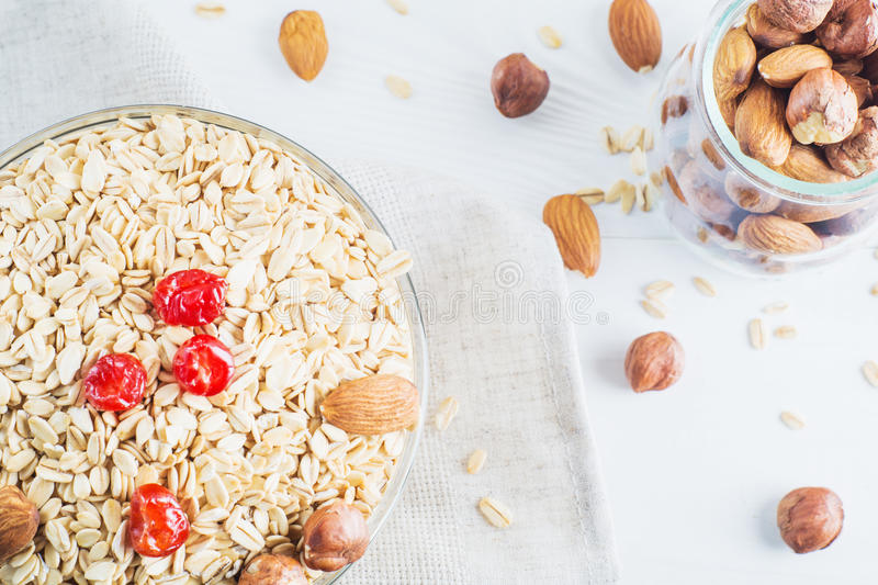 Healthy food. Ingredients for healthy breakfast. On white wooden background. Oatmeal, dried cherry and nuts, closeup, top view. The concept of natural organic stock photo