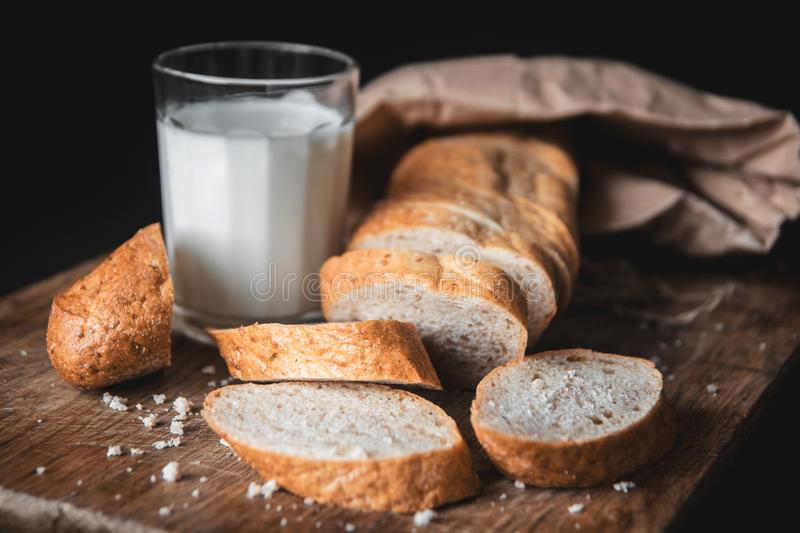 Healthy food. Long loaf of rural bread with two cut-off pieces lie on a wooden chopping board and a glass of fresh milk. Dark background. Horizontal shot stock photography
