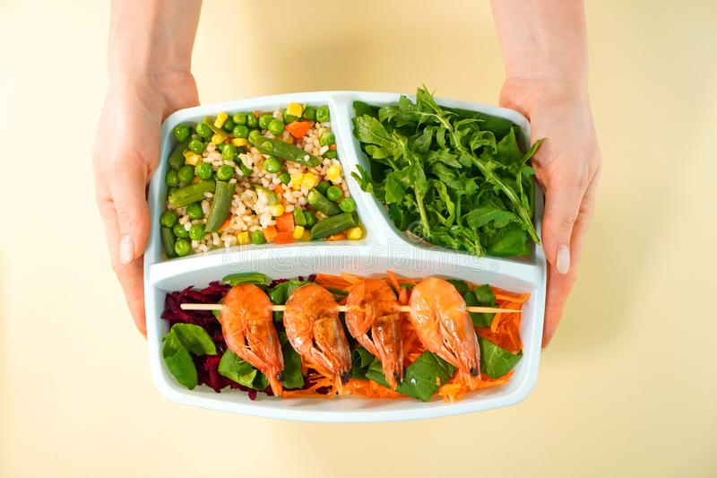 Healthy food in lunch box in female hands top view. Shrimps, rice, salad, arugula and vegetables are in the delivery container. royalty free stock photo