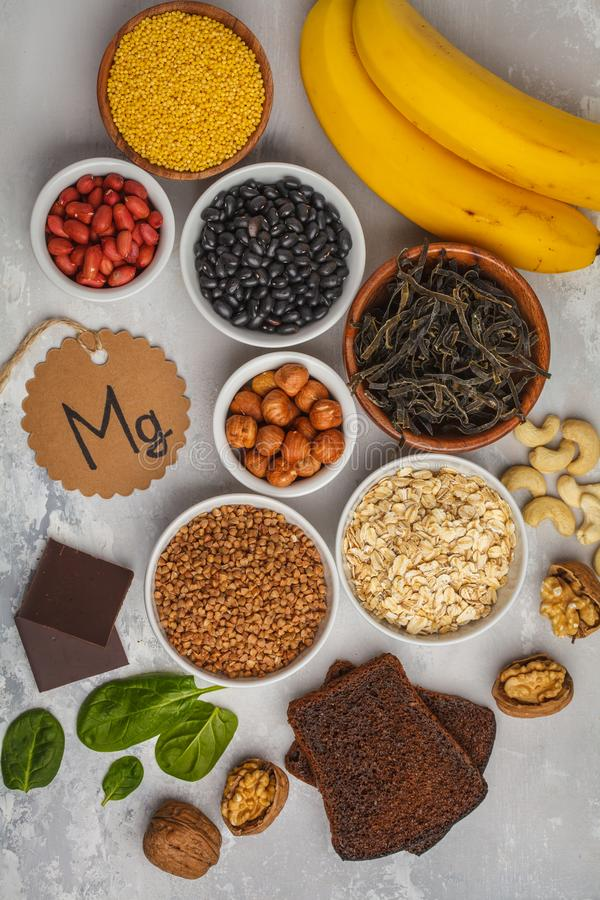 Healthy food nutrition dieting concept. Assortment of high magnesium sources. Banana chocolate spinach, buckwheat, nuts, beans, o. At royalty free stock photography