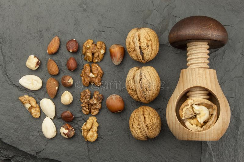 Healthy food - nuts. Walnut kernels and whole walnuts on slate. Walnuts and wooden nutcracker. Advertising on walnuts royalty free stock photography