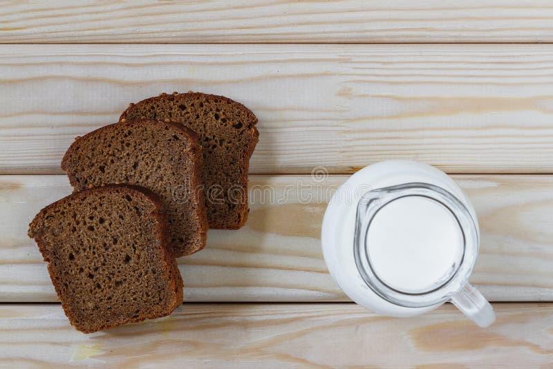Milk, breakfast, bread, black, jug, pitcher, dark, table, food, royalty free stock images