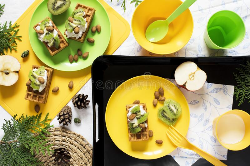 Healthy food. Picnic in nature. Breakfast with waffles, kiwi, almond, soft cheese, apple, milk on white background. Top view, flat stock photography
