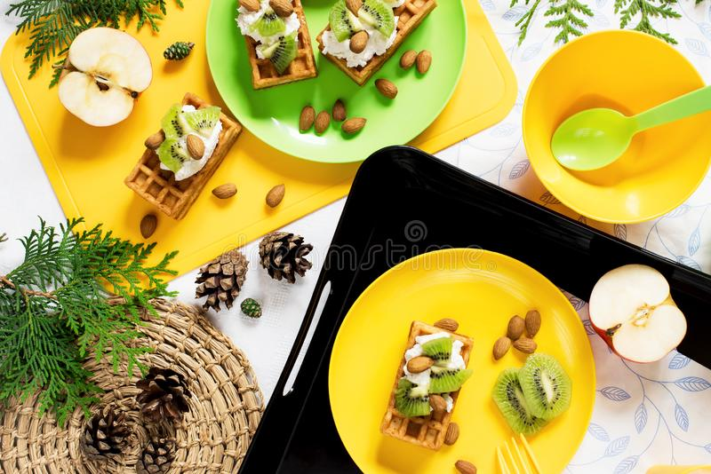 Healthy food. Picnic in nature. Breakfast with waffles, kiwi, almond, soft cheese, apple, milk on white background. Top view, flat royalty free stock photo