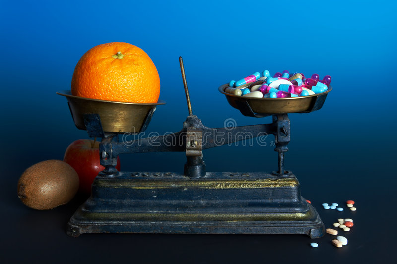 Healthy food or pills. Balance weighing healthy food, fruit, and diet or vitamin pills royalty free stock images