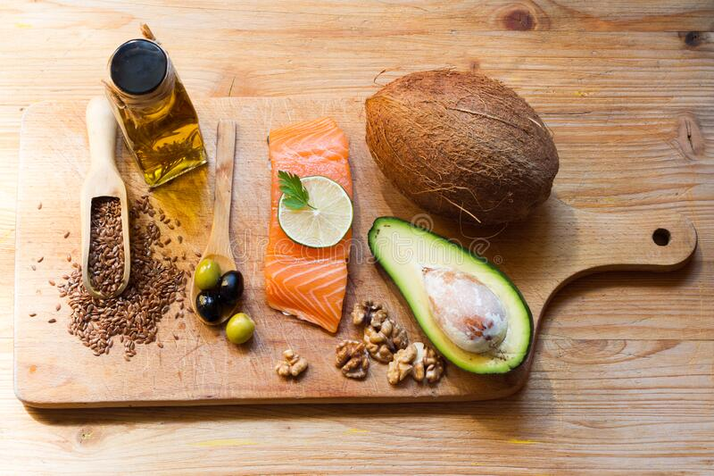 Healthy food. Products with healthy fats on wooden board stock photography