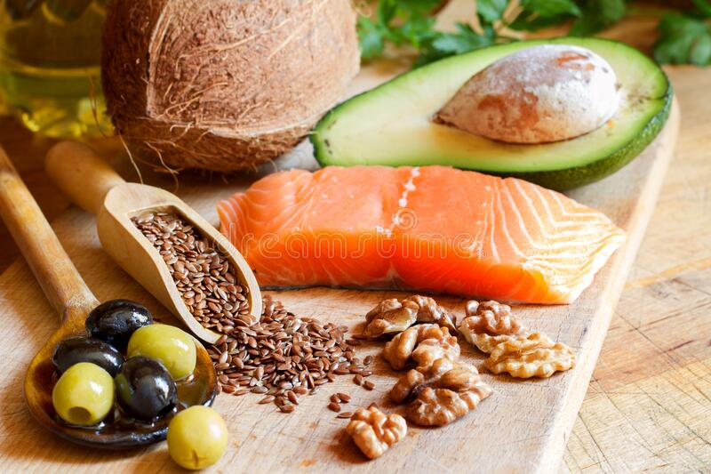 Healthy food. Products with healthy fats on wooden board stock photo