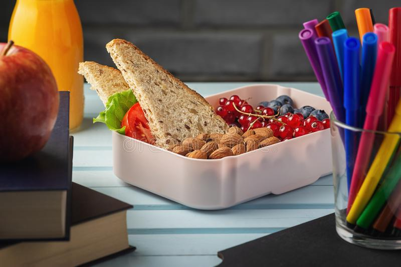 Healthy food for school lunch. On the table among the textbooks is a school lunch, in a box are almonds, red currants royalty free stock photos