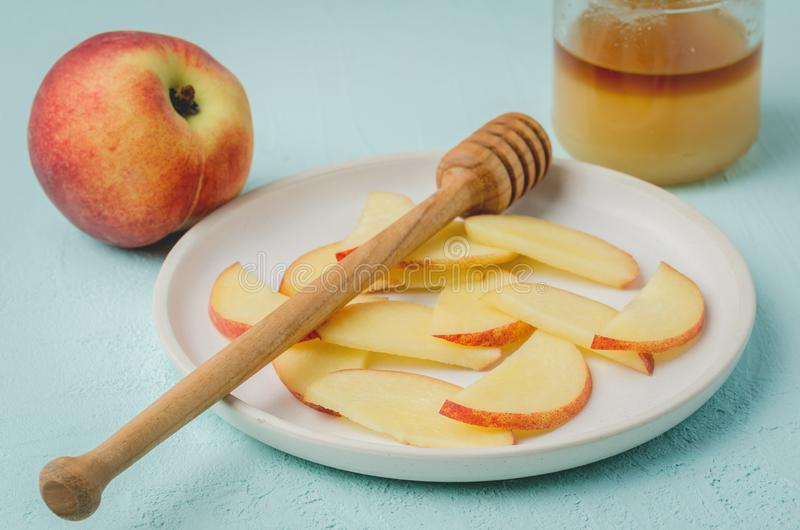 Healthy food. Sliced peach with honey in a bowl, selective focus royalty free stock photography