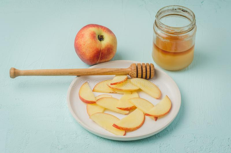 Healthy food. Sliced peach with honey in a bowl, selective focus. Blue background royalty free stock image