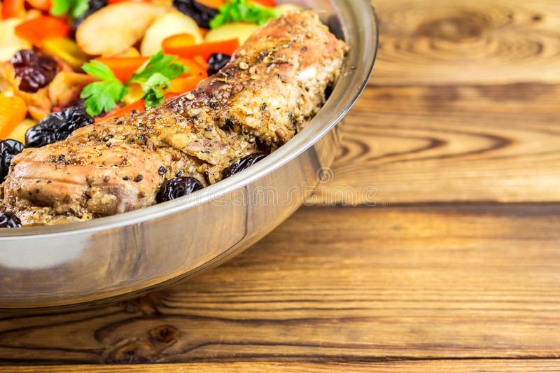 Healthy food, stewed pork meat with various colorful vegetables in pan on wooden background, selective focus. Space for text royalty free stock photo