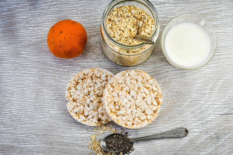 Healthy food. Still life composition with healthy food. Milk, mandarin rise crackers ,oat flakes ,vintage tea spoon and chia seed on white background stock images