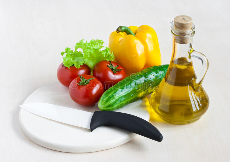 Healthy food still life with white ceramic knife. On light gray table stock images