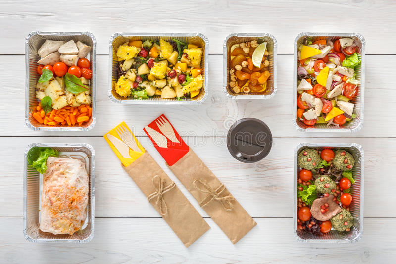 Healthy food take away in boxes, top view at wood. Healthy restaurant food background. Eating right concept. Diet daily meals delivery. Fitness nutrition royalty free stock images