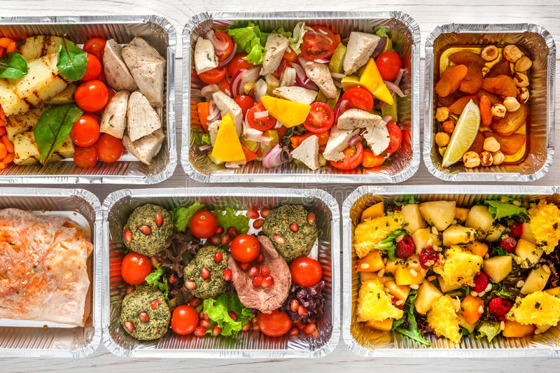 Healthy food take away, top view at wood background. Healthy food background. Take away of natural organic creative meals in foil boxes. Fitness nutrition, meat stock photo