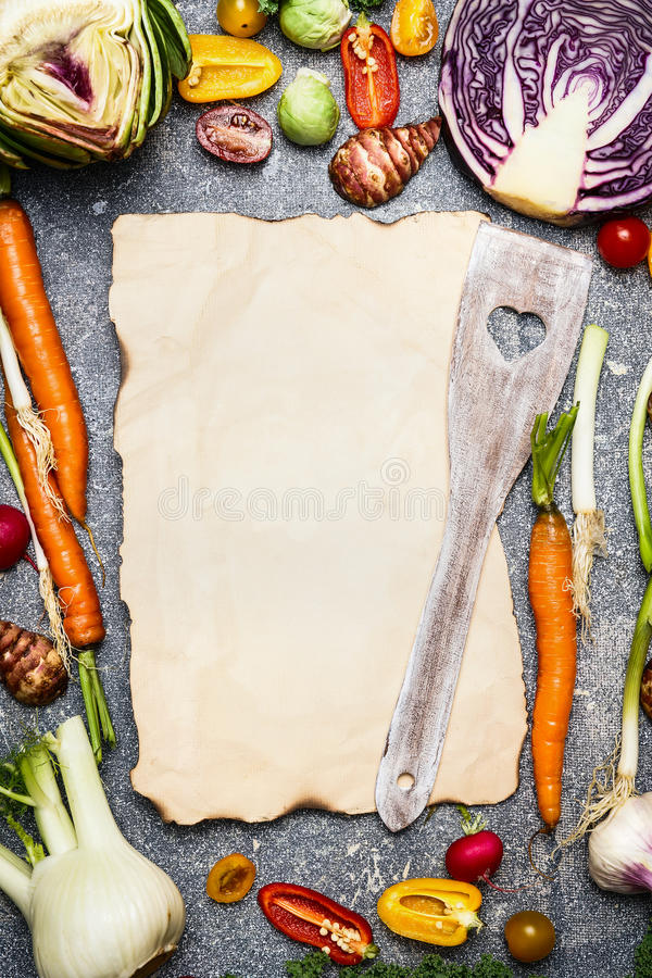 Healthy food and tasty vegetarian cooking background with assortment of colorful farm vegetables around blank sheet of paper with. Wooden spoon , top view royalty free stock photos