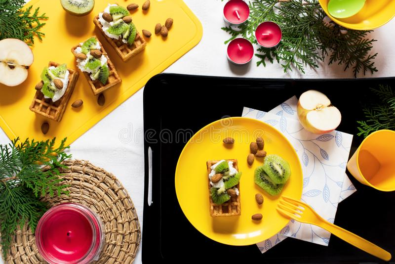 Healthy food. Top view decoration holiday background. Flat lay. Breakfast with waffles, kiwi, almond, soft cheese, apple, milk on stock image