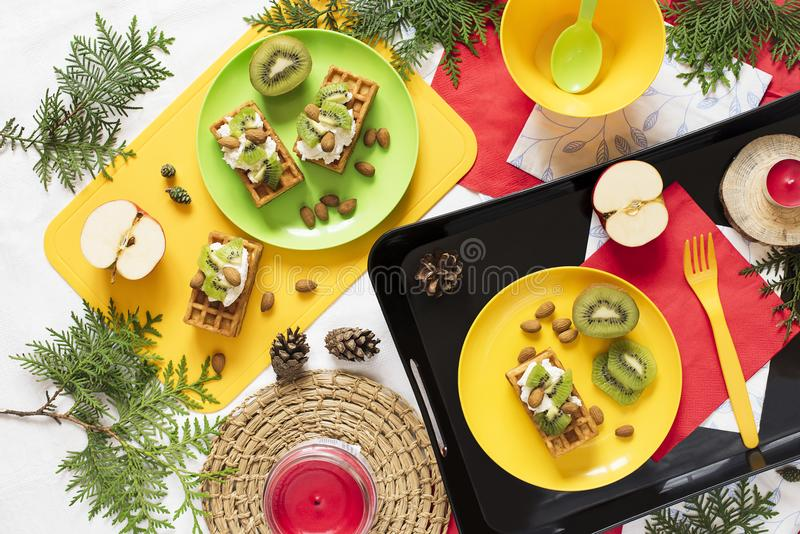 Healthy food. Top view decoration holiday background. Flat lay. Breakfast with waffles, kiwi, almond, soft cheese, apple, milk on stock photo