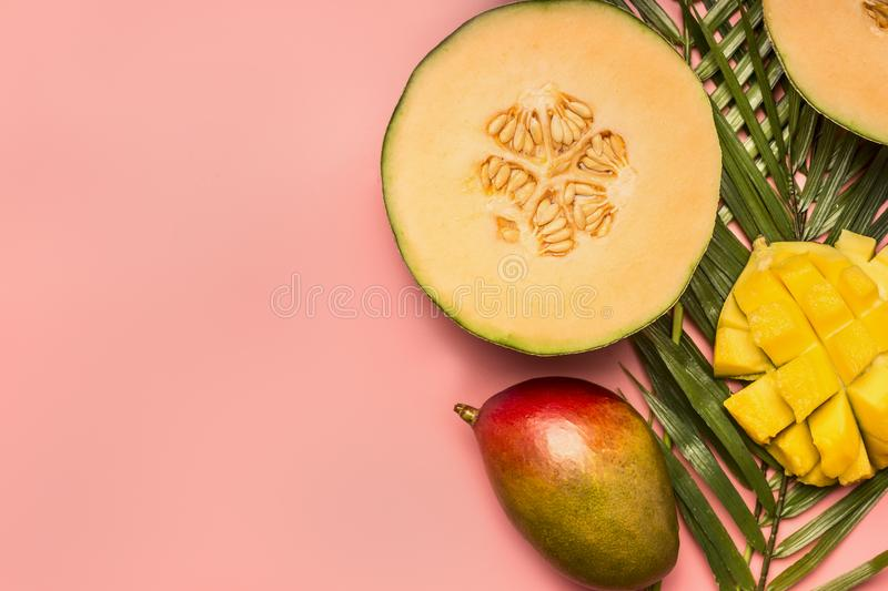 Healthy food, tropical fruits, mango, melon on a monstera leaf with smoothies on a pink background, space for text flat lay. Healthy food, tropical fruits, mango royalty free stock photos