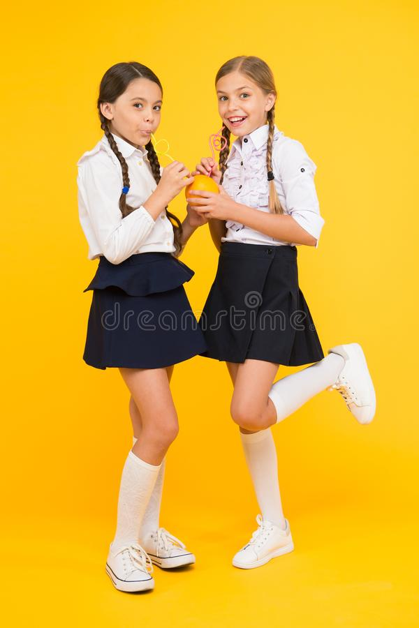 Healthy food. Vital habits. Fruits glucose energy source. School lunch. Vitamin nutrition. Fresh fruit school. Girls. Kids school uniform drinking orange fruit stock photo
