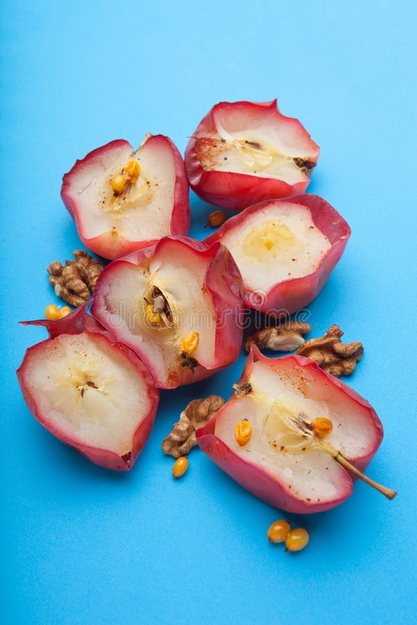 Healthy food for weight loss from red baked apples with nuts and vinegar on a blue background, vertically stock photos