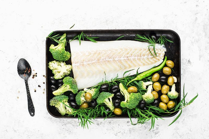 Healthy food: wild organic fresh sea white cod fish with broccoli, tarragon, onions, olives on a baking sheet. The stock photo