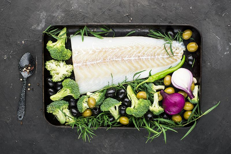 Healthy food: wild organic fresh sea white cod fish with broccoli, tarragon, onions, olives on a baking sheet. The stock image