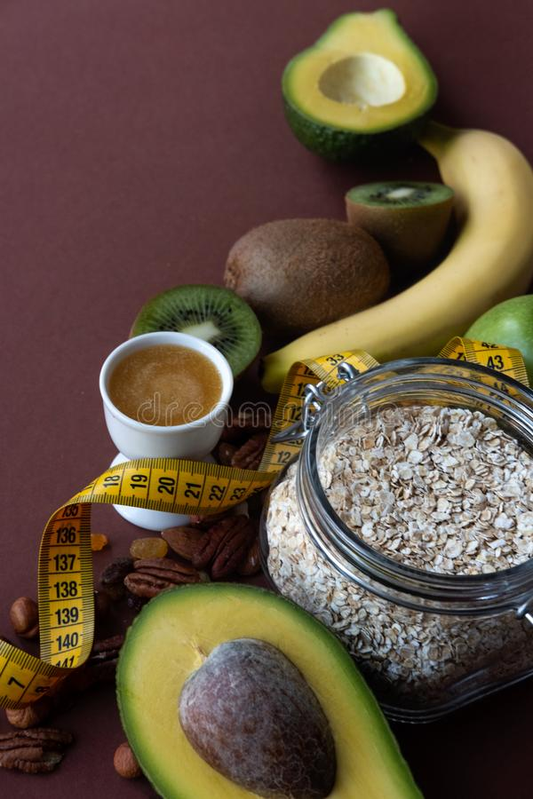 Healthy food and yellow tape measure over brown table. Fitness and health concept. royalty free stock photography