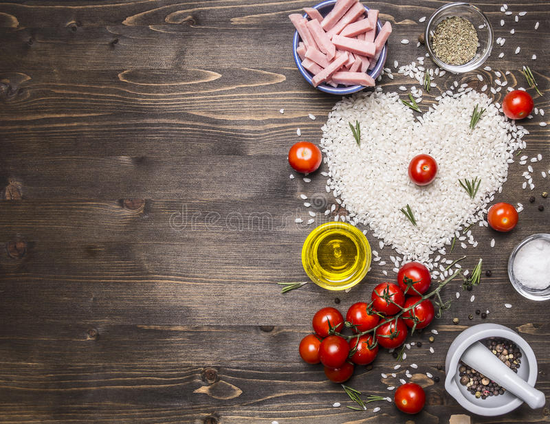 Healthy foods, cooking and concept risotto with ham, oil, cherry tomatoes, rice tiled heart, valentines day border ,place text royalty free stock photos
