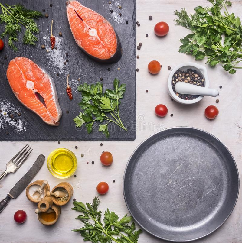 Healthy foods, cooking and sport concept Two fresh salmon steak with herbs and spices on cutting board stone, laid near cherry t royalty free stock photography
