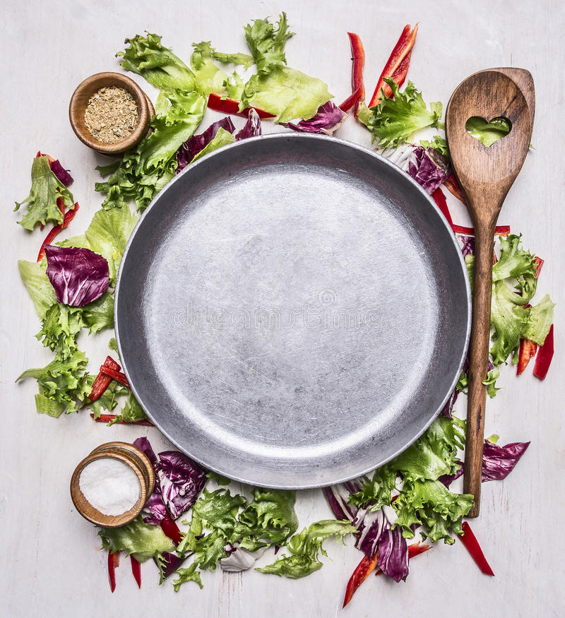 Healthy foods, cooking and vegetarian concept lettuce with a wooden spoon, salt and pepper, laid out around pan place for text. Healthy foods, cooking and stock photo