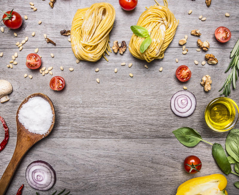 Healthy foods, cooking and vegetarian concept pasta with flour, vegetables, oil and herbs on wooden rustic background top view bor stock photography