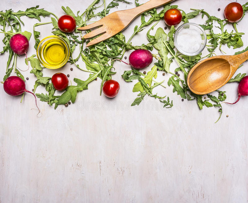 Healthy foods, cooking and vegetarian concept salad with cherry tomatoes, radishes, spices wooden spoon and fork border ,place royalty free stock images