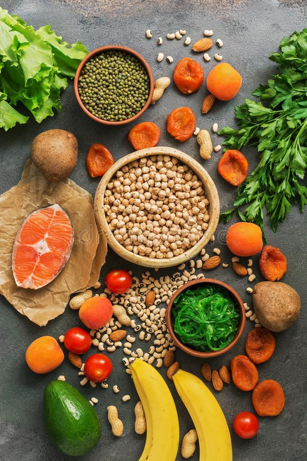 Healthy foods high in potassium. A variety of legumes, salmon, fruits, vegetables, dried apricots, seaweed chuka and nuts on a royalty free stock photography