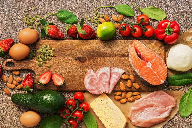 Healthy foods low in carbohydrates. Keto diet concept. Salmon, chicken, vegetables, strawberries, nuts, eggs and tomatoes, cutting. Board. Healthy foods low in royalty free stock image