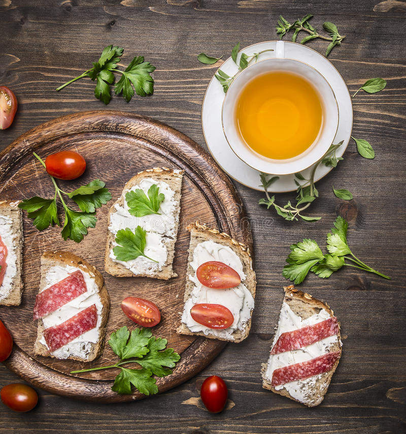 Healthy foods sandwiches with red fish, cherry tomatoes and salami on a cutting board, cup of tea with thyme on wooden rust royalty free stock image