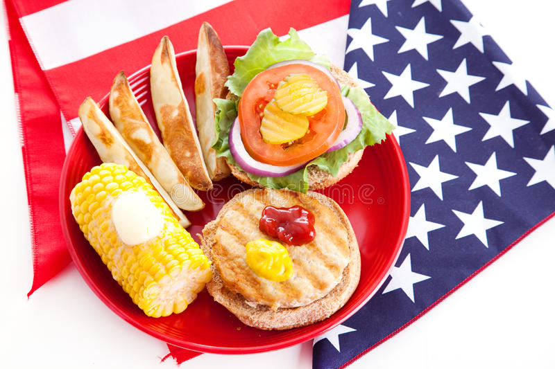 Healthy Fourth of July Picnic. Healthy turkey burger on whole grain bun, with baked potato wedges and corn on the cob, for Fourth of July picnic royalty free stock image