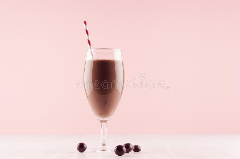 Healthy fresh chocolate smoothie with sweety and striped straw on pastel pink background, copy space. stock image