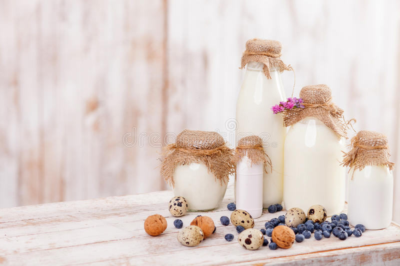 Healthy fresh food is necessary for your life. Close up of bottles of milk products, eggs, nuts and berry on the table. Copy space in left side stock photos