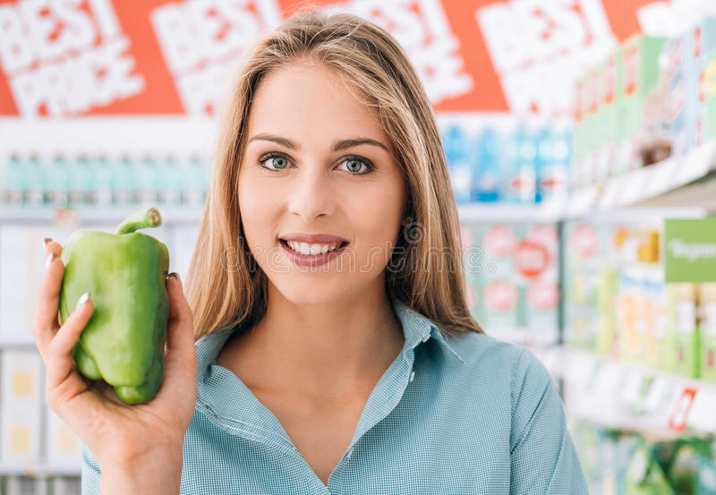 Healthy fresh food. Smiling young woman shopping at the supermarket, she is holding a fresh pepper, food freshness and diet concept royalty free stock images