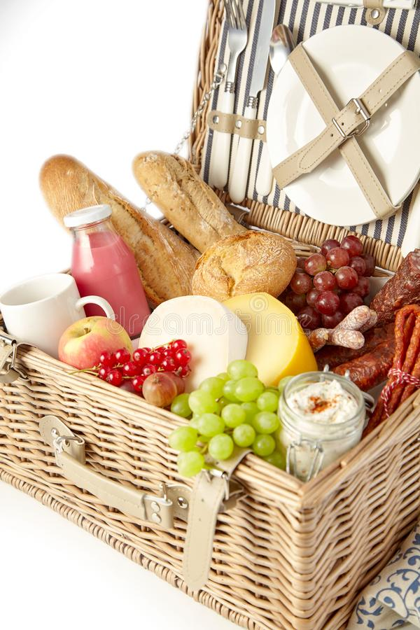 Healthy fresh fruit, bread and cheese in a hamper. Healthy fresh fruit, spicy sausages bread and cheese in a hamper with a bottle of juice or smoothie ready for stock photography