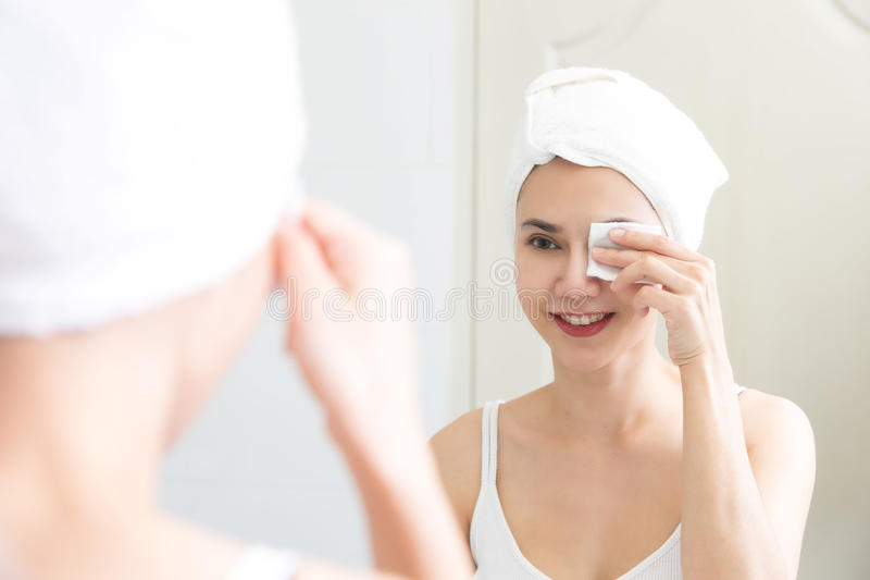 Healthy fresh girl removing makeup from her face with cotton pad stock photos