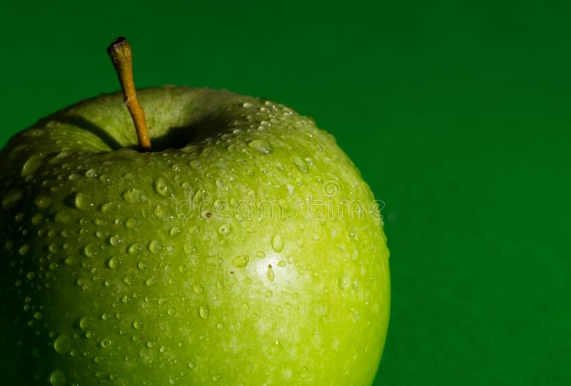 Fresh green apple partially seen with water drops on green background. royalty free stock images