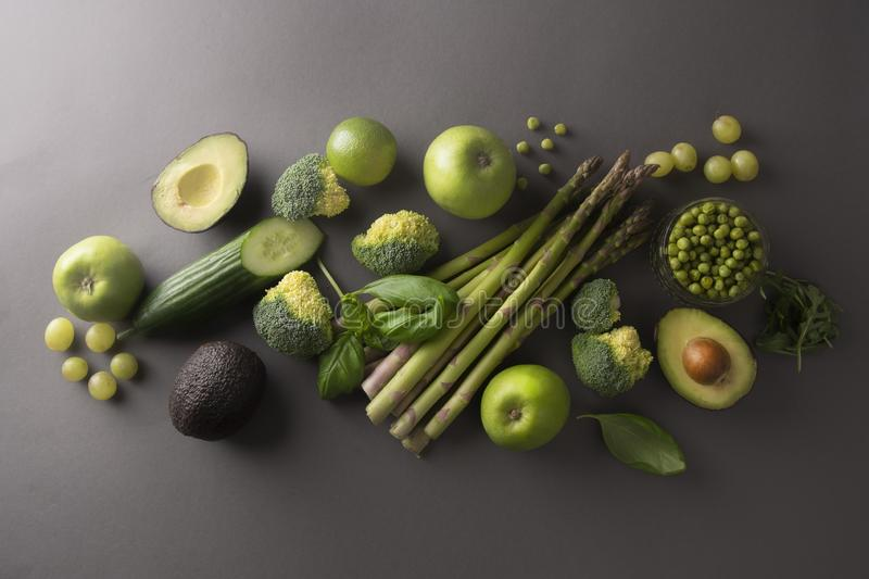 Healthy fresh green vegetables and fruits: asparagus, cucumber, basil, green peas, avocado, broccoli, lime, apples, grapes,. Healthy fresh green vegetables and royalty free stock photos