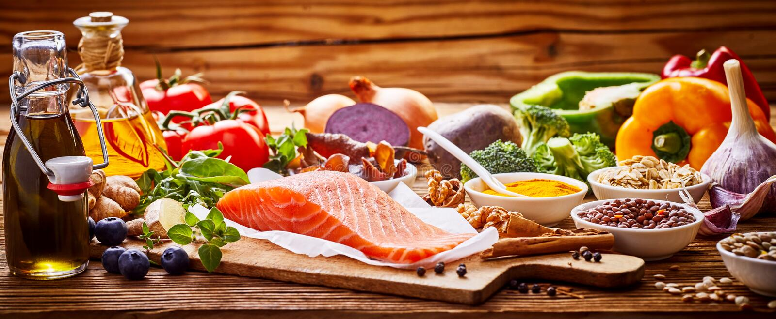 Healthy fresh raw food for the heart in a banner. Format on rustic wood with salmon, assorted spices, herbs, nuts, peppers, blueberries, tomato, onion, broccoli royalty free stock images