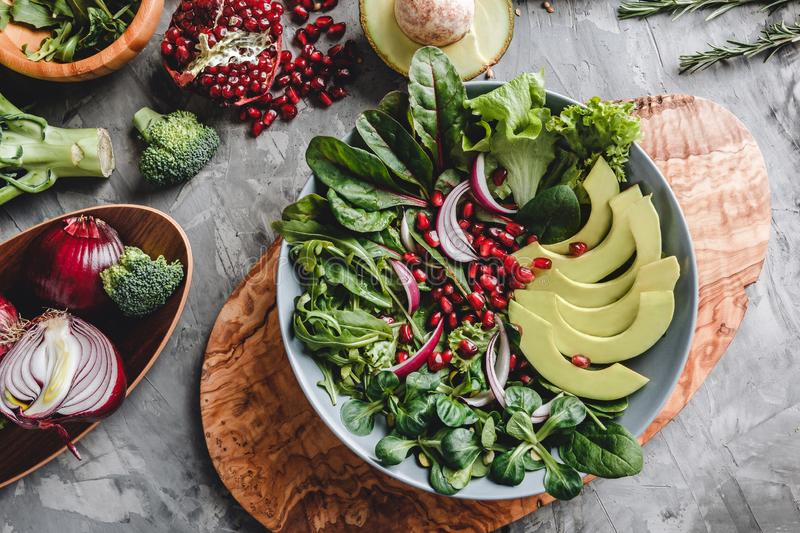 Healthy fresh salad with avocado, greens, arugula, spinach, pomegranate in plate over grey background. royalty free stock photo