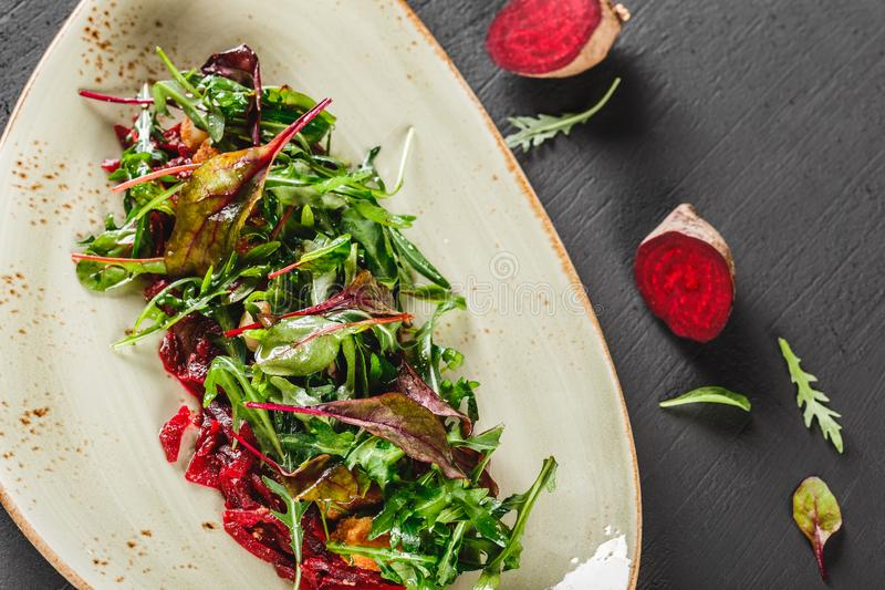 Healthy fresh salad with baked beets, greens, arugula, spinach and croutons in plate over dark table. Healthy vegan food, royalty free stock photography
