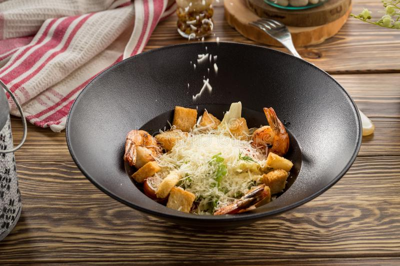 Healthy fresh vegetable Caesar Salad with shrimp, parmesan Cheese and Croutons on wooden table royalty free stock photography