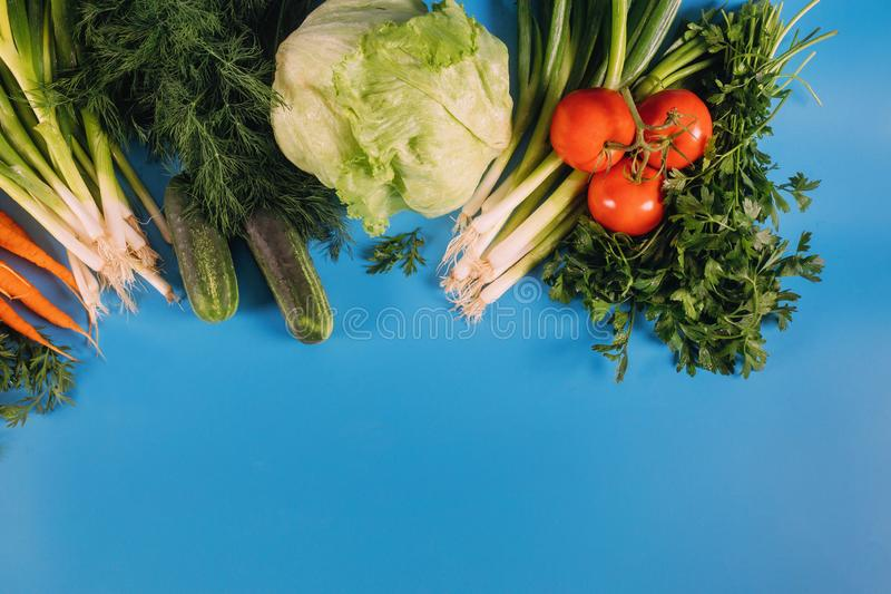 Healthy fresh vegetables on blue table stock images