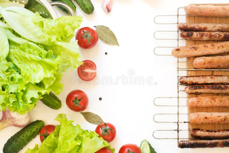 Healthy fresh vegetables for salad and roasted sausages on grill. Raw green lettuce, greens, tomato. Top view. Copy space. Food co royalty free stock photo